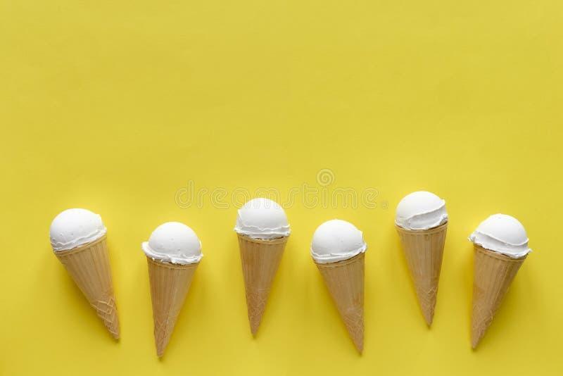 Rad av vaniljglasskottar på guling royaltyfria foton