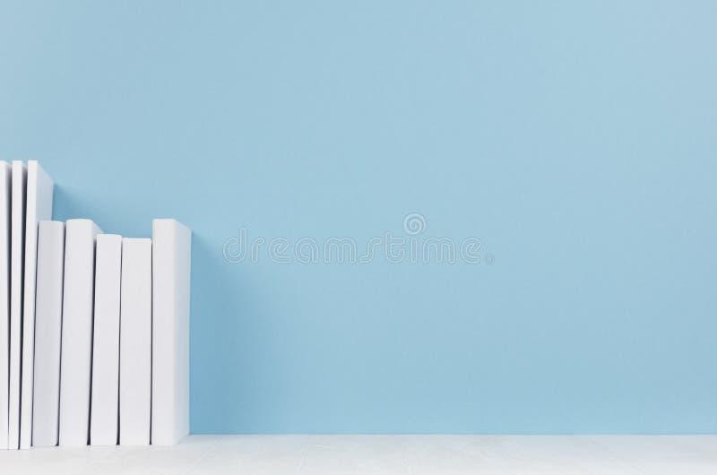 Rad av vita böcker på det ljusa wood skrivbordet och mjuk pastellblåttbakgrund med kopieringsutrymme royaltyfri foto