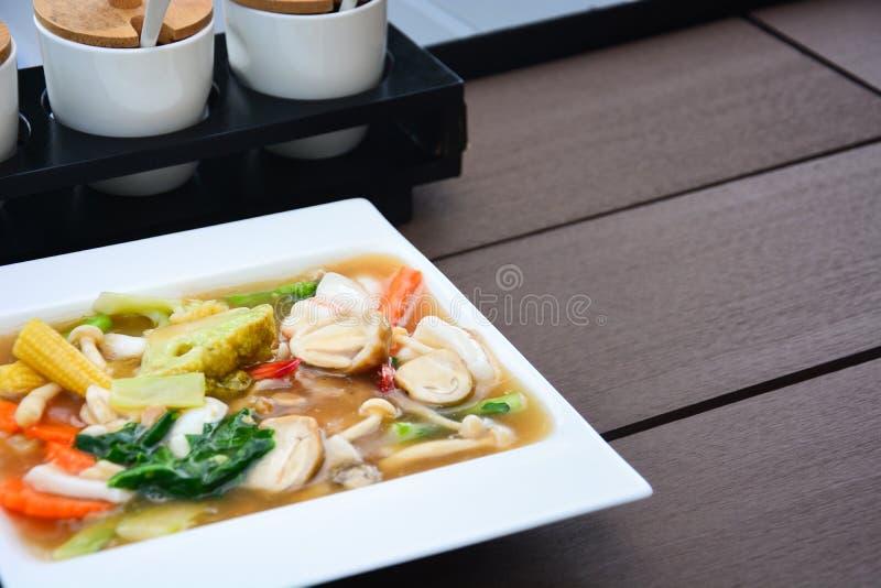 'Rad Na' är en blandning av kinesiska och thailändska livsmedel, friterade nudlar med skaldjur på träbord, kopieringsutrymme royaltyfria foton