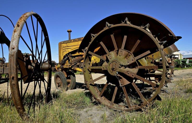 Rad und Ansätze eines alten Traktors in einem Autofriedhof lizenzfreie stockfotos
