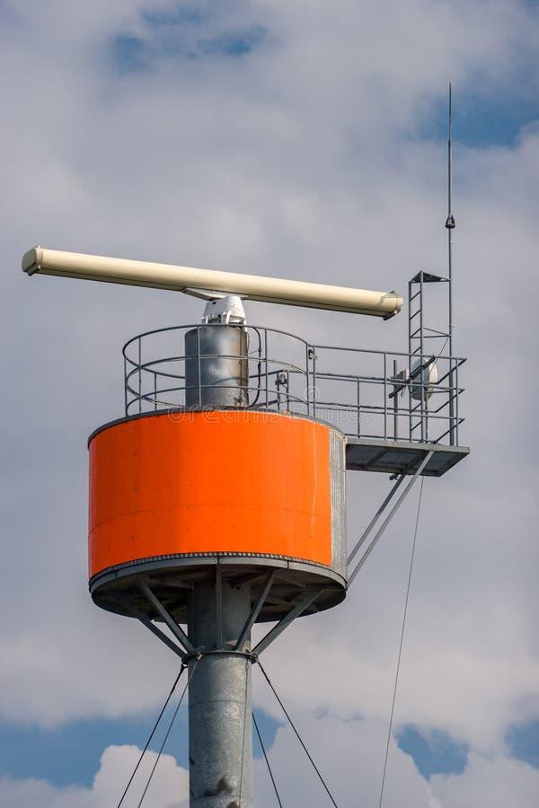 Radar met zender op een ronde staalpijler tegen de hemel stock foto