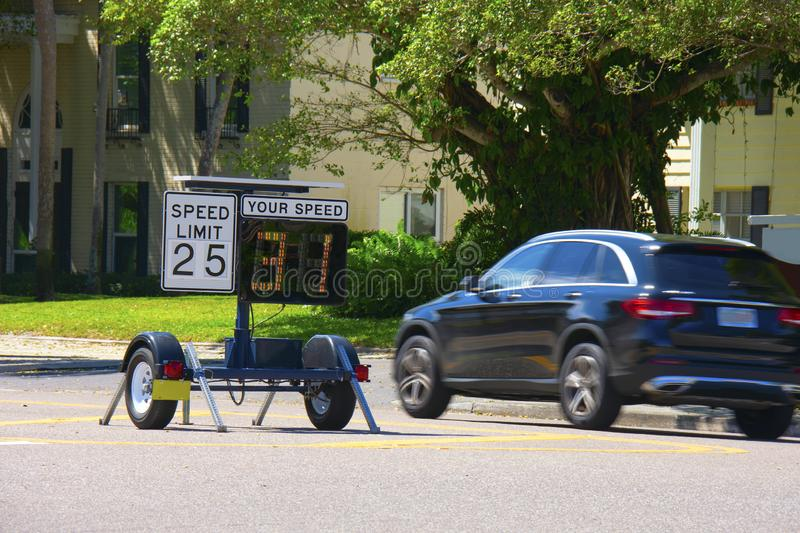 Radar speed limit indicator sign showing a passing car is speeding as it drives down the road. Radar speed limit indicator sign monitored by the police showing royalty free stock photos