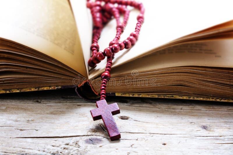 Radbandet pryder med pärlor från rött trä med korset i en gammal bok på en rusti royaltyfria bilder