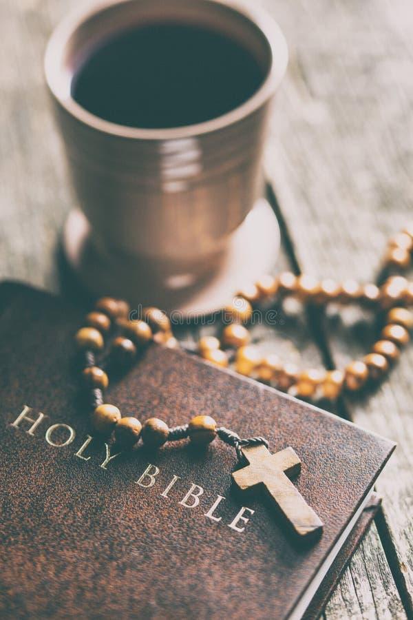 Radbandpärlor, helig bibel och kopp av vin arkivfoto