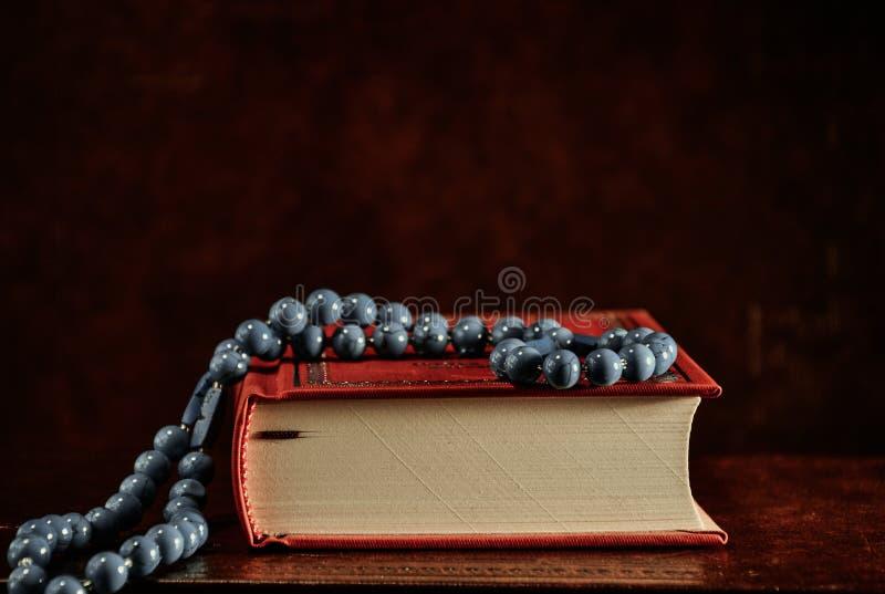 Radbandpärlor och röd helig bibel på tabellen royaltyfri bild