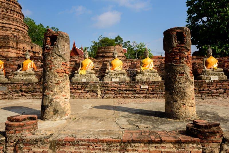 Raden av Buddhastatyer med fördärvar kolonnen på Wat Yai Chai Mongkhon i Ayutthaya arkivfoton