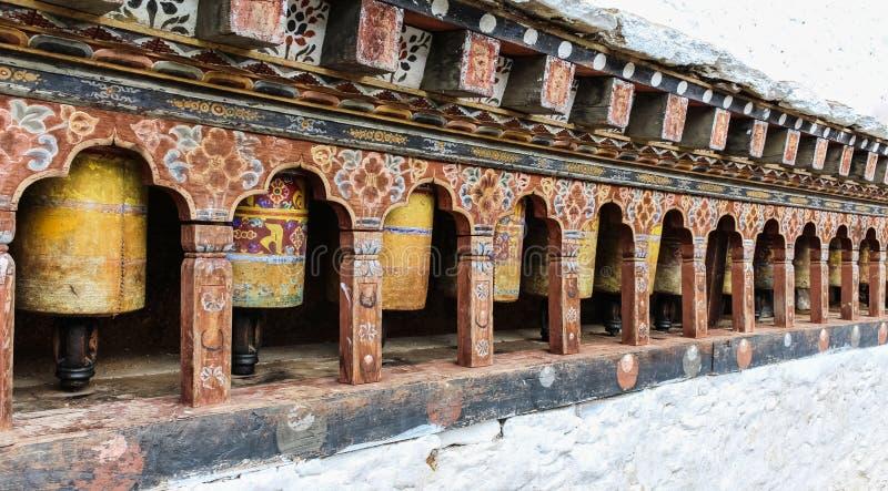 Raden av den traditionella gula buddistiska bönen rullar in väggen, Bhutan royaltyfri bild