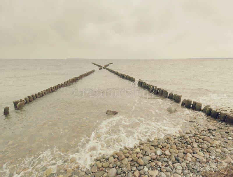 Raden av gamla trähögar som vågbrytaren framme av den steniga stranden royaltyfri fotografi