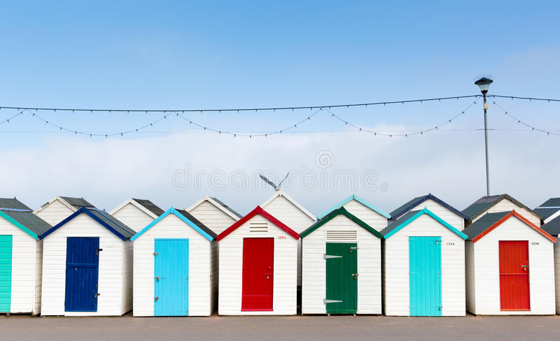 Raden av stranden förlägga i barack med färgglade röda blåa och gröna dörrar royaltyfri bild
