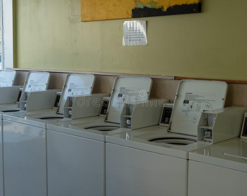 Raden av tvätterimyntet fungerade tvätterimaskiner inom en laundroma arkivfoton