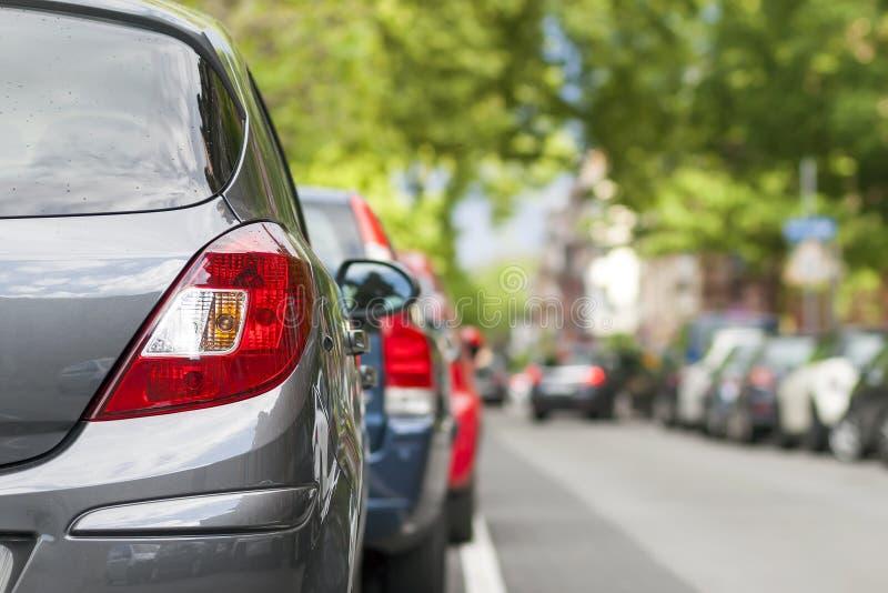 Rader av bilar som parkeras på vägrenen i bostads- område arkivbilder