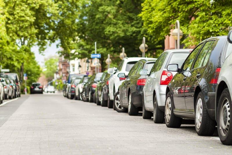 Rader av bilar som parkeras på vägrenen i bostads- område royaltyfri bild