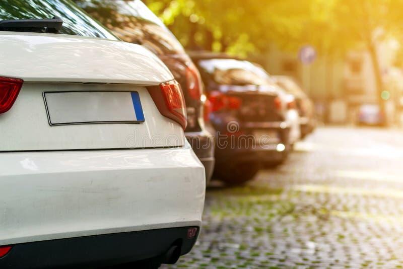 Rader av bilar som parkeras på vägrenen i bostads- område fotografering för bildbyråer