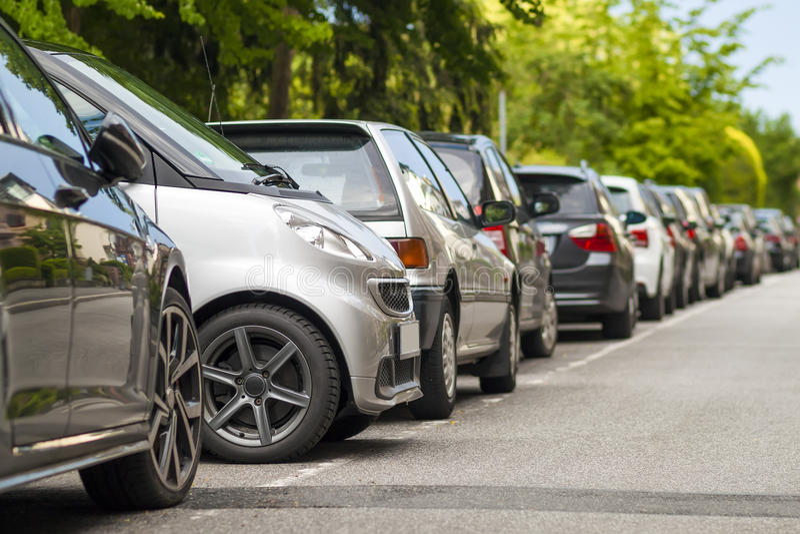 Rader av bilar som parkeras på vägrenen i bostads- område sma royaltyfri fotografi