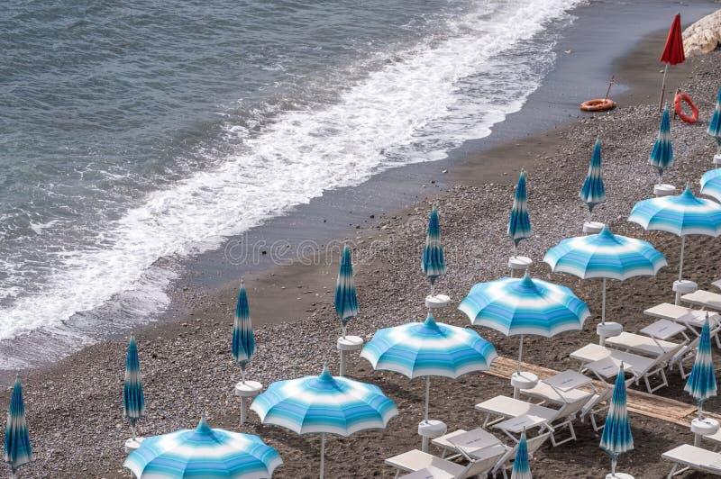 Rader av blåa och vita slags solskydd och sunbeds på stranden på Atrani på den Amalfi kusten, Italien royaltyfri fotografi