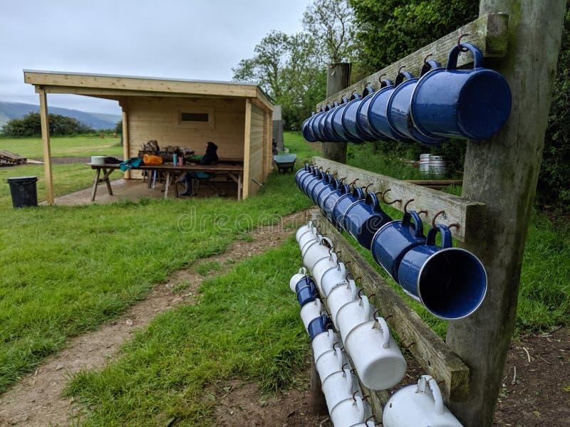 4 rader av den campa koppen för blå och vit emalj rånar i ett fält arkivbilder