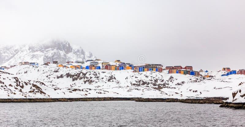 Rader av den färgrika inuit som bor hus av den Sisimiut staden, på det brant, vaggar royaltyfri bild