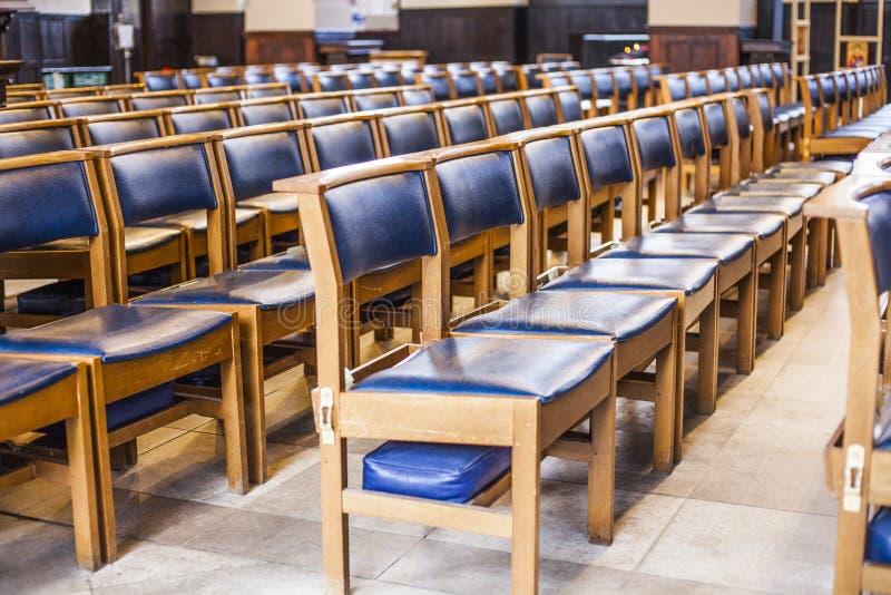 Rader av empy stolar i kyrkan Blåa stolar i korridoren arkivbild