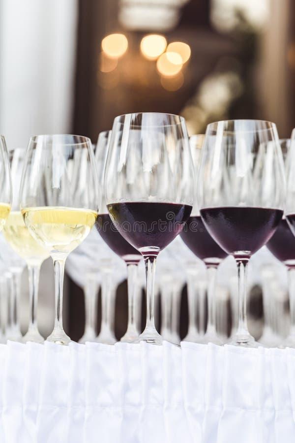 Rader av exponeringsglas för rött och vitt vin på den vita bordduken royaltyfri bild