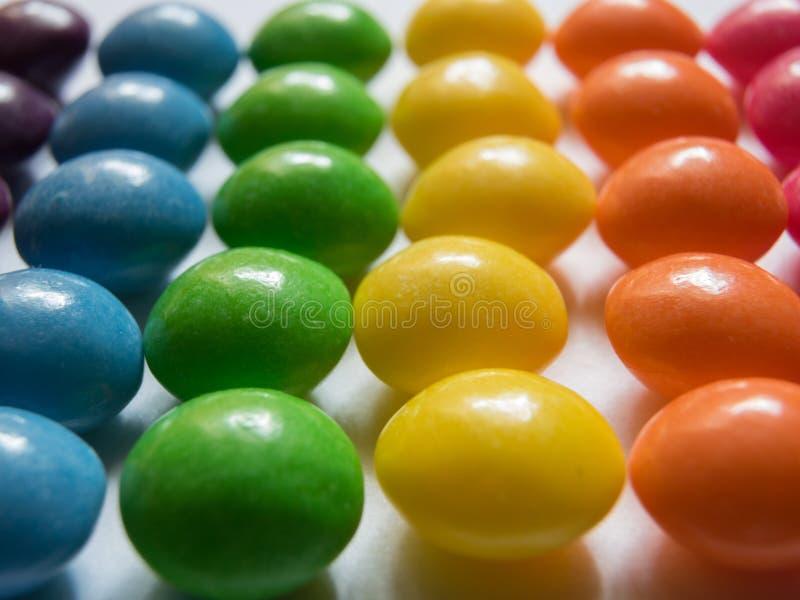 Rader av färgrika godisar på vit bakgrund royaltyfri fotografi