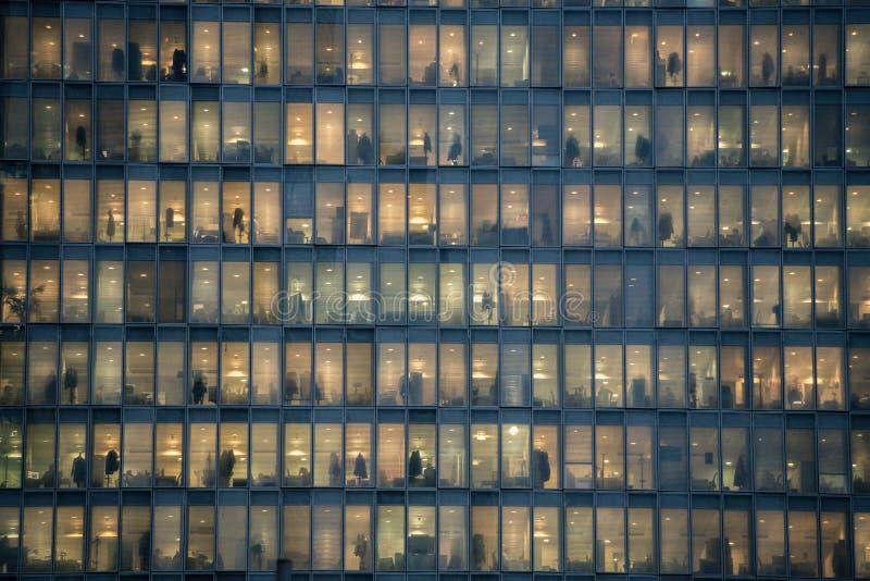 Rader av fönster med folk som arbetar i inre av en kontorsbyggnad på natten i Milan, Italien royaltyfri bild