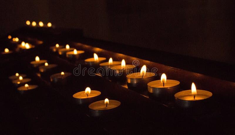 Rader av glödande stearinljus i mörker Stearinljus med brinnande falme Kyrklig garnering Religion- och trobakgrund arkivbilder