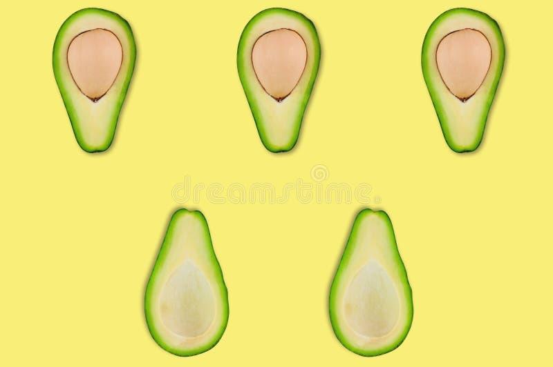 Rader av halvor med och utan kärnor av den organiska avokadot i mitt av den gula tabellen i kök eller marknad royaltyfria foton