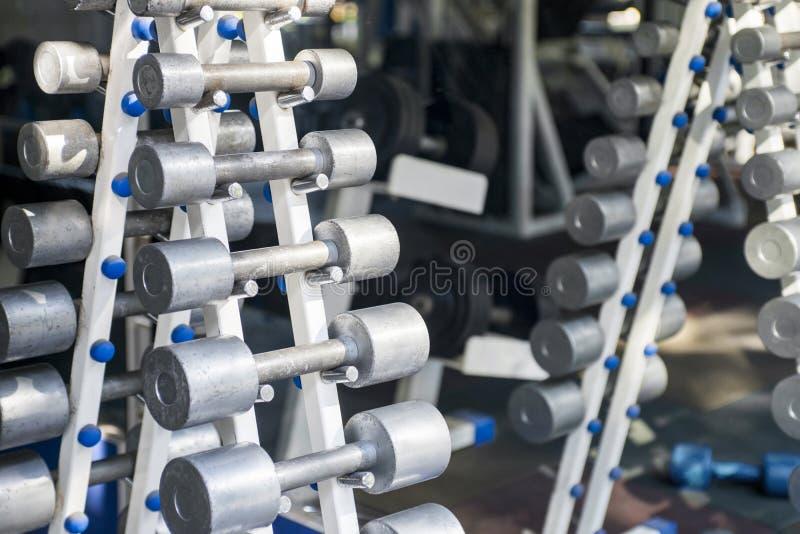 Rader av hantlar i idrottshallen Hanteluppsättning Stäng sig upp många metallhantlar på kuggen i sportkonditionmitt royaltyfria bilder