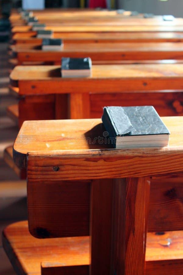 Rader av kyrkliga bänkar med biblar Tomma träkyrkbänkar Selektivt fokusera arkivfoton