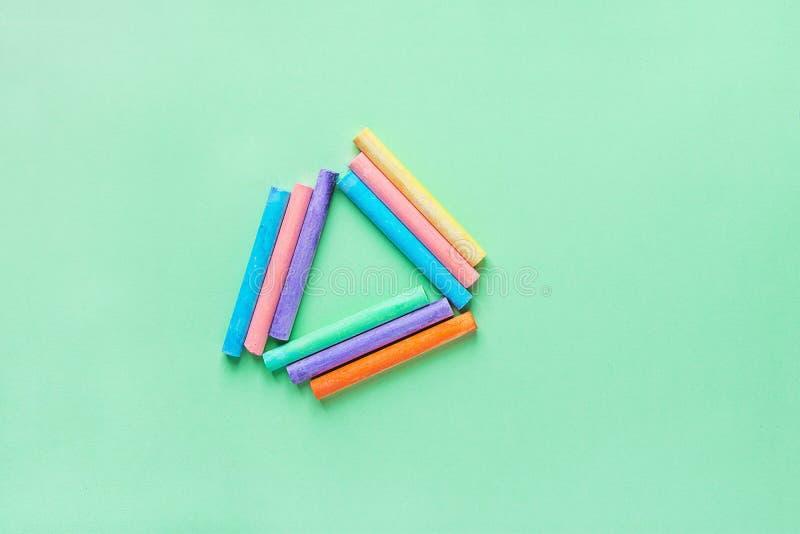 Rader av mångfärgade Chalksfärgpennor som är ordnade i triangel på turkosbakgrund Ungar för hantverk för grafisk design för affär arkivbilder