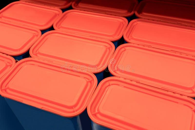 Rader av röda plast- lock med blåa behållare arkivbilder