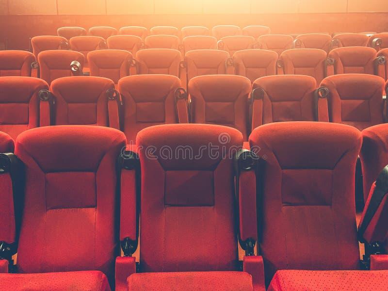 Rader av röda platser eller stolar i filmsalong med ljus effekt royaltyfria foton
