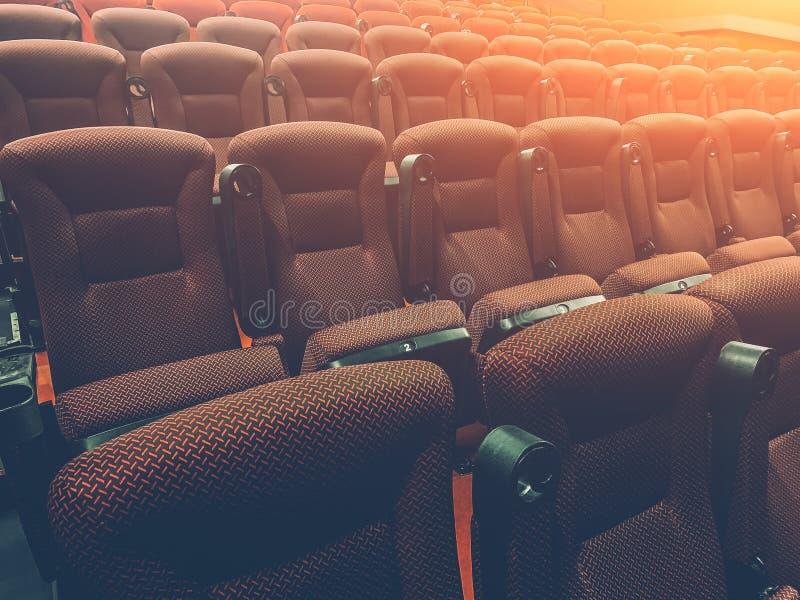 Rader av röda platser eller stolar i filmsalong med ljus effekt royaltyfri foto