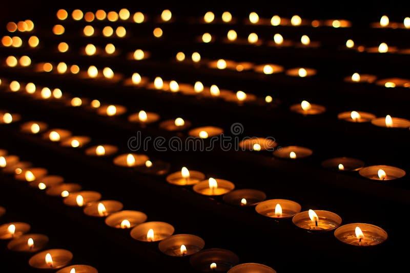 Rader av stearinljus i mörkt ställe royaltyfri foto