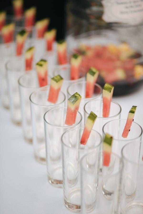 Rader av tomma exponeringsglas och vattenmelon som är förberedda för mottagande royaltyfria bilder
