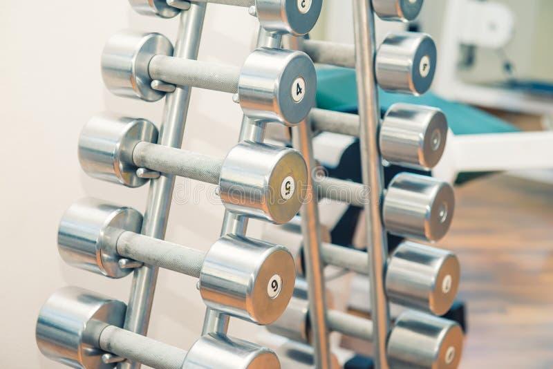 Rader av tunga hantlar för metall på ställning i sportidrottshallen, sjukgymnastikklinik Sjukgymnastikmitt Sportutrustning för ut arkivfoto