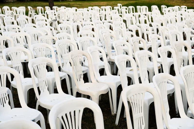 Rader av vita plast- utomhus- stolar royaltyfria foton