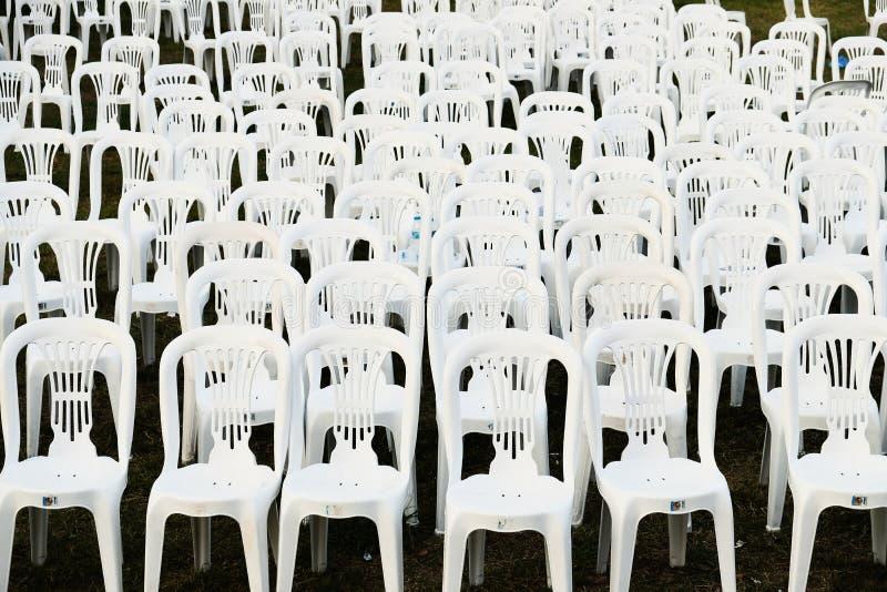 Rader av vita plast- utomhus- stolar arkivbild