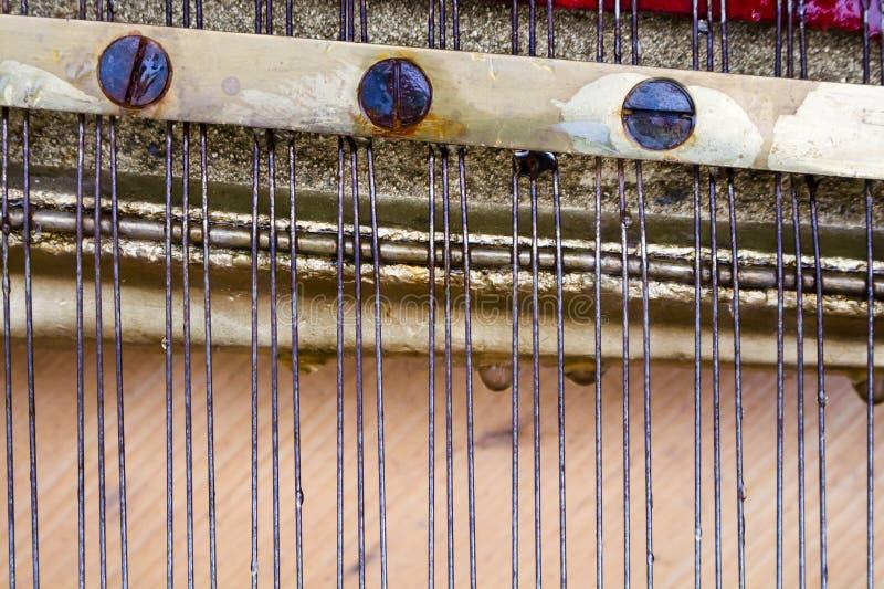 Rader och skruvar inom det gamla pianot royaltyfria bilder