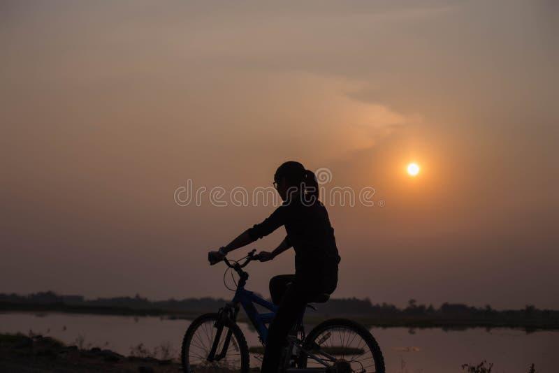 Radfahrende Hände der Frau bei Sonnenuntergang stockfoto