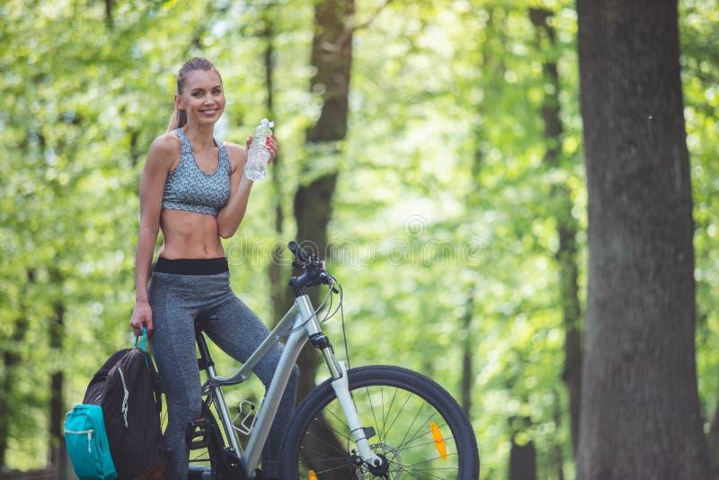Radfahrenfrau erneuert mit Getränk stockfotografie