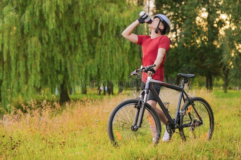 Radfahrenkonzept: Junger kaukasischer männlicher Radfahrer, der Wasser Bruch hat stockbilder