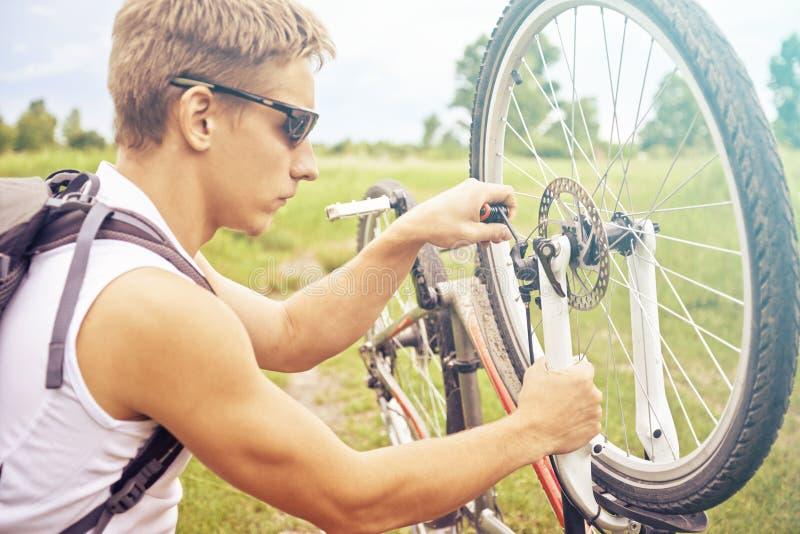Radfahrer überprüft Rad des Fahrrades stockfotografie