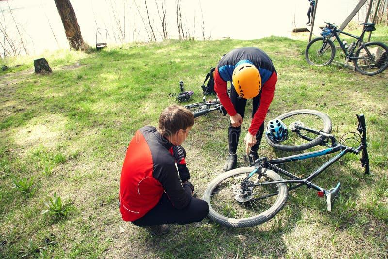 Radfahrer auf einem Halt Problem mit Mountainbike und Reparatur stockfotos