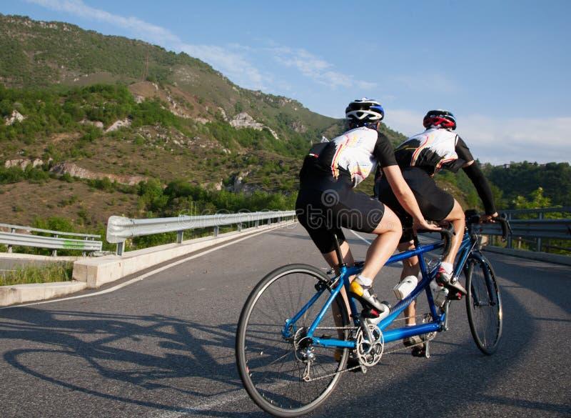 Radfahrer auf einem Tandemfahrrad, das aufwärts auf eine Gebirgsfahrbahn fährt lizenzfreies stockbild