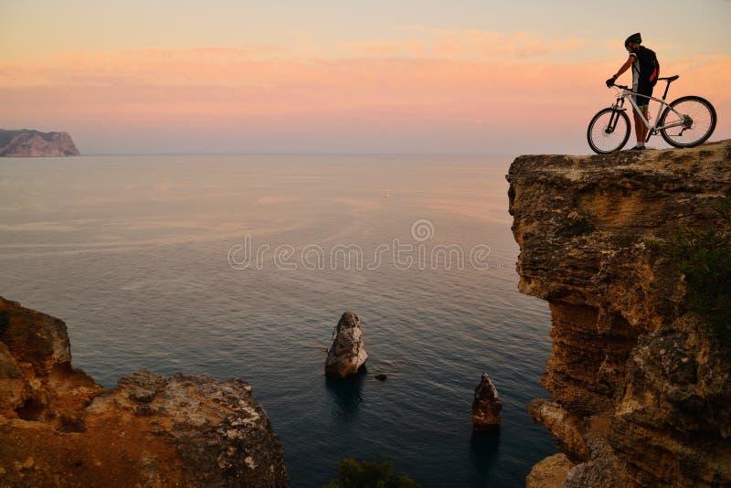 Radfahrer auf einer Klippe im Hintergrund des Meeres bei Sonnenuntergang stockfotos