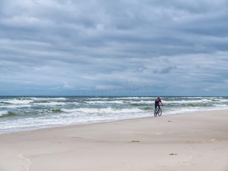 Radfahrer auf sandigem Strand stockfotografie