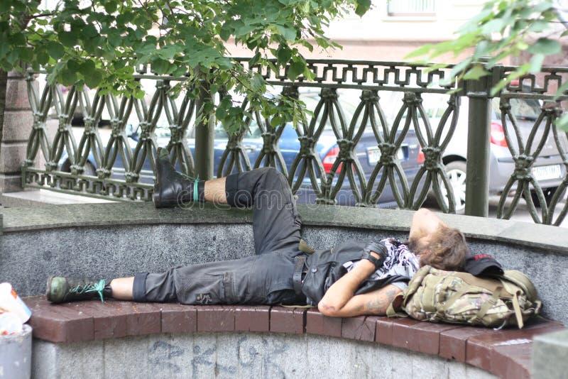 Radfahrer, der auf einer Bank schläft lizenzfreie stockfotografie