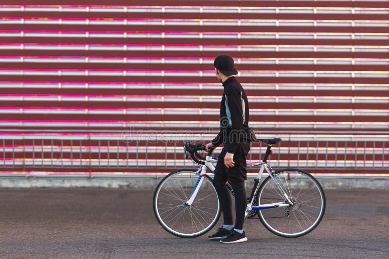 Radfahrer in der dunklen Sportkleidung, stehend mit einem Fahrrad auf dem Hintergrund eines roten Schirmes und betrachten es lizenzfreie stockfotografie
