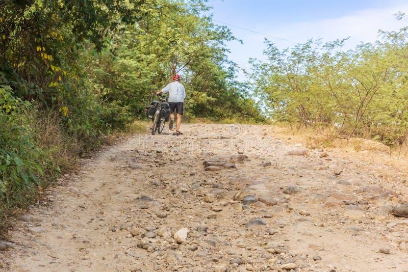 Radfahrer, der mit Fahrrad auf einem steilen Schotterweg V 280 nahe Rio geht lizenzfreie stockfotos